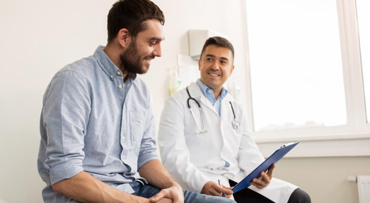 Young man patient sat with a male doctor on a bed in a white room. Both smiling supportively.